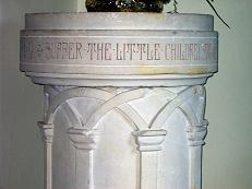 The white carved stone baptismal font, a gift from the Sunday School, first used in July 1908, and incorporating an 18th century pewter basin.